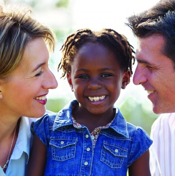 smiling girl with adoptive parents
